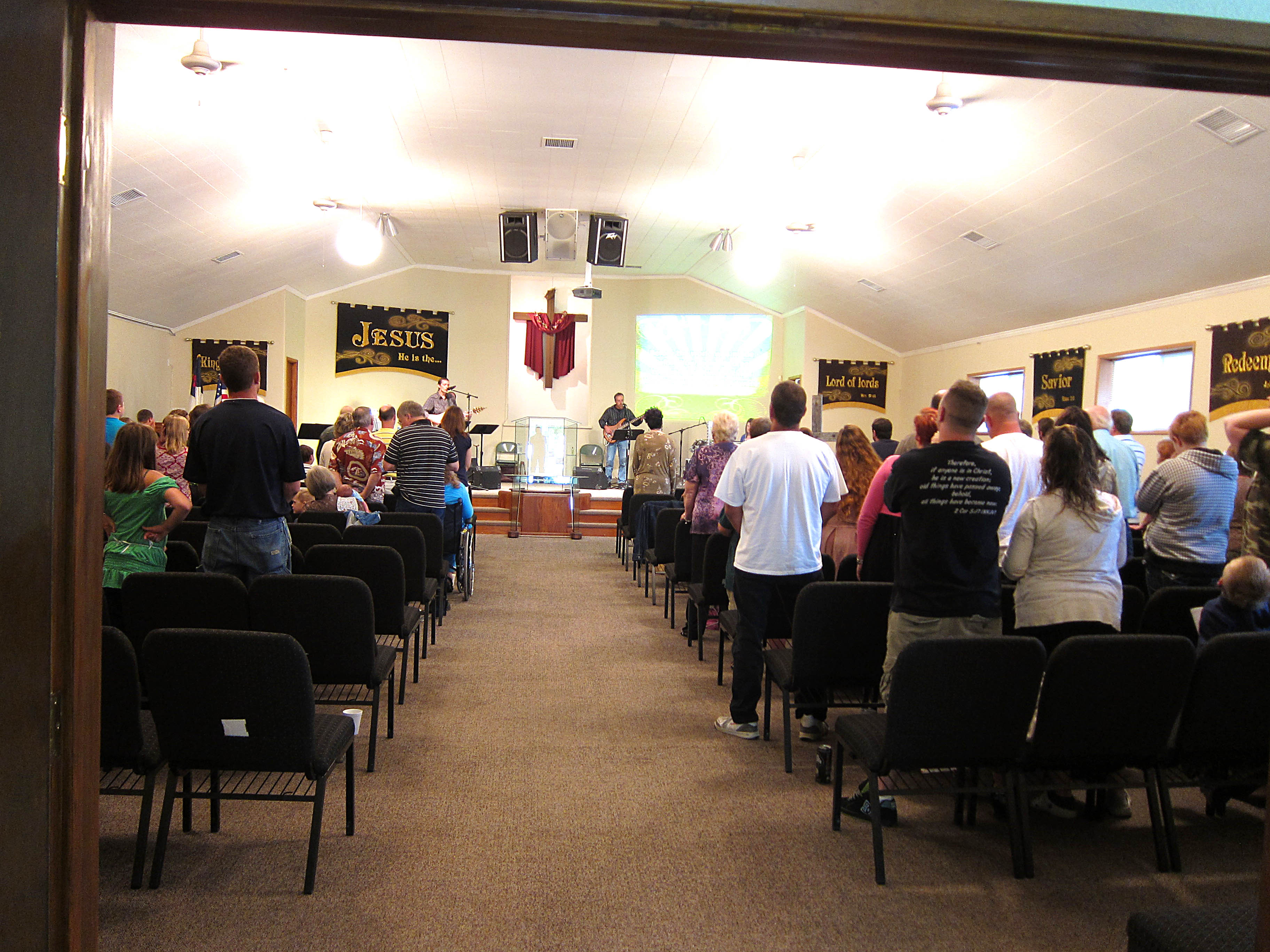 People enjoying worship with the new church decorations that fixed the blank church walls